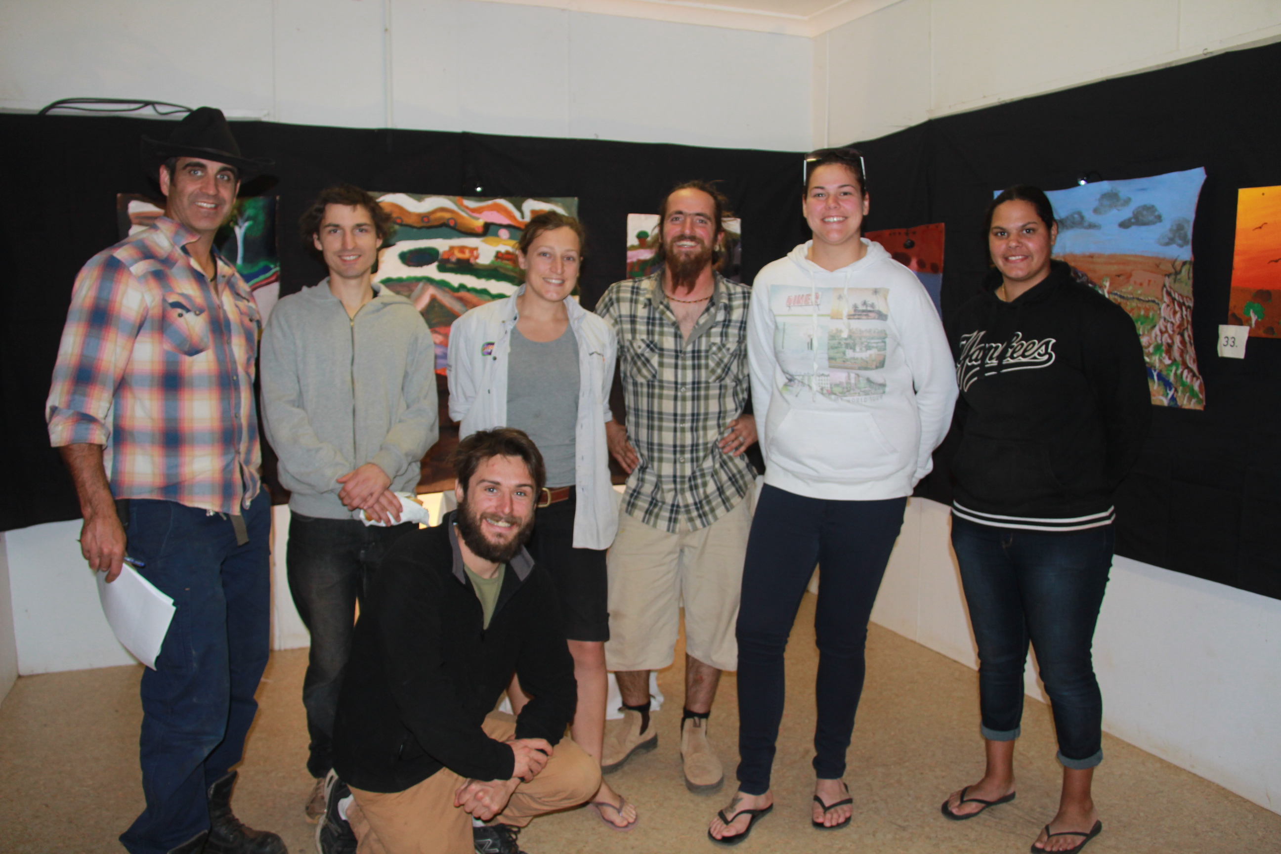 Exhibition Visitors. From to left to right: Damien Thornber, Carlo McAbee, Emily Minchin, Leo Ollivier, Ebony Humble, Larissa Bennell & Josh McHale (at front) - The Desert Feet Tour and Ngurra Kujunka mob enjoying the vibe at the exhibition
