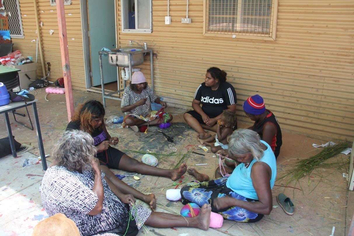 Lily Long (centre pink beanie) teaching the ladies to weave